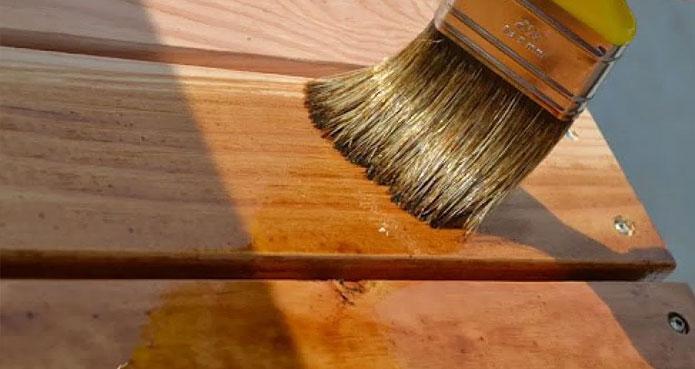Application d'une teinture au pinceau sur une planche en bois